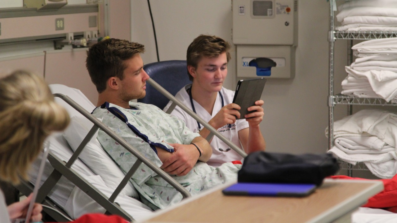 Students using an iPad in the simulation lab